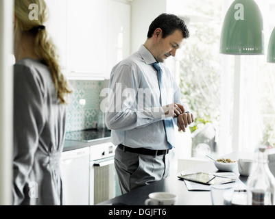 Mature businessman checking time in kitchen - Stock Photo
