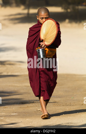 A novice monk with fan, lunchbox and collection bowl in Bagan in Myanmar. - Stock Photo