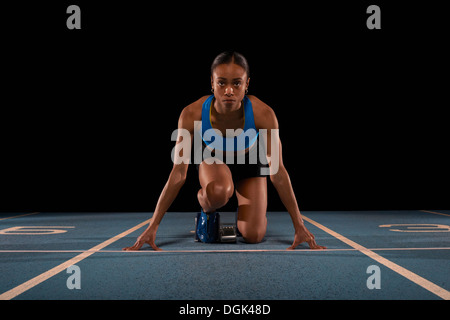 Young female athlete on starting blocks - Stock Photo