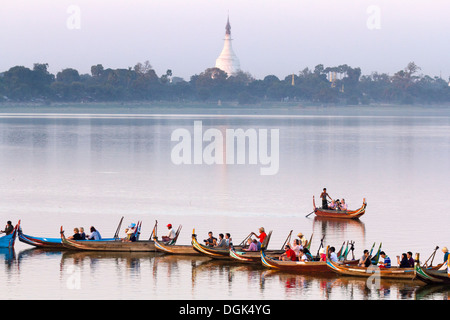 Tourist boats lining up on Taungthaman Lake in Myanmar to view sunset over U Bein Teak Bridge. - Stock Photo