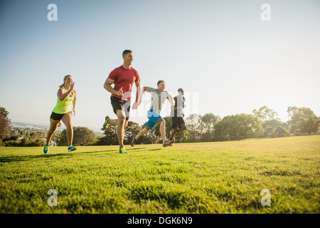 Group of young adults on training run in field - Stock Photo