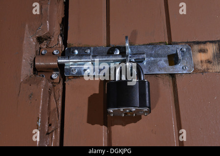 Black modern padlock securing a wooden painted door - Stock Photo