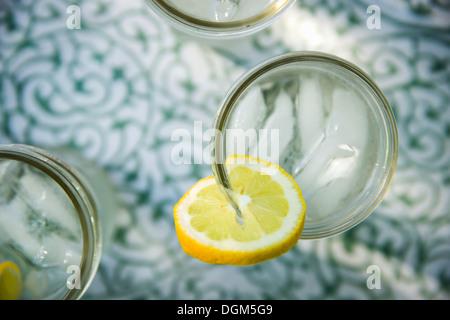 Making lemonade Overhead shot of lemonade glasses fresh slice of lemon in edge of glass Organic lemonade drinks - Stock Photo