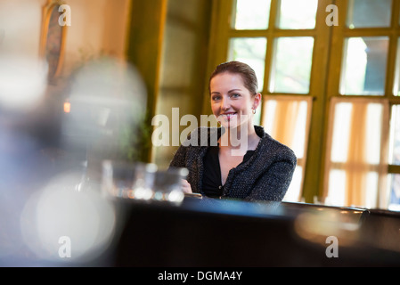 Business people outdoors. A woman sitting alone at a table in a coffeeshop or restaurant. - Stock Photo