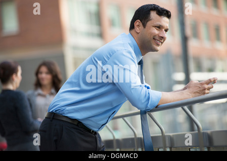 Business people outdoors. A latino businessman in shirt and tie, leaning on a railing. Relaxing. - Stock Photo