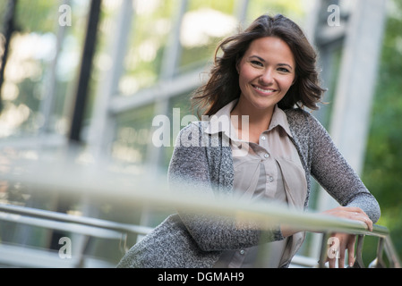 Business people outdoors. A businesswoman in a light grey jacket, leaning on a railing smiling. Relaxing. - Stock Photo