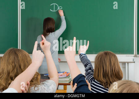 School children raising their arms to answer during class, Germany - Stock Photo