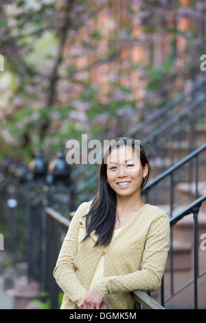 A young woman with long black hair, leaning on a railing at the bottom of a flight of steps. - Stock Photo