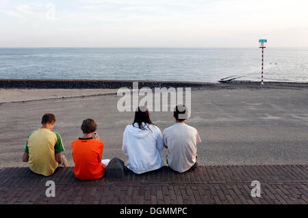 Young people sitting on the dike in the evening, looking on the sea, Westkapelle, Walcheren, Zeeland, Netherlands, - Stock Photo