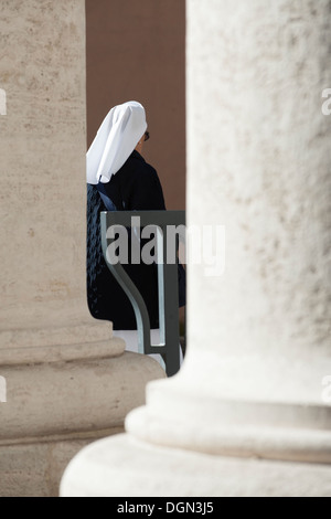 Nun walk in St Peter's colonnades - Stock Photo