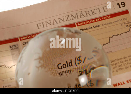 Glass globe on business newspaper, lettering 'gold - Stock Photo