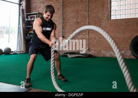 Male bodybuilder using ropes in gym - Stock Photo
