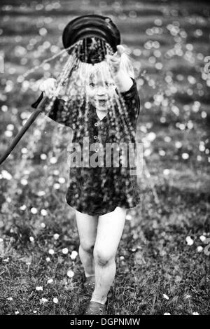 Young boy playing with a watering hose in a garden - Stock Photo