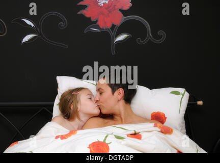 Mother, 35 years, and daughter, 9 years, in bed - Stock Photo