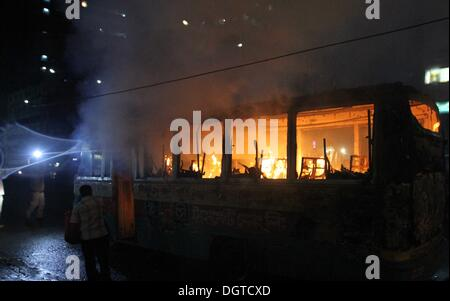 Dhaka, Bangladesh. 25th Oct, 2013. A bus set on fire by Bangladeshi demonstrators burns on a street during a protest - Stock Photo