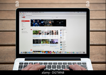 The YouTube website on a MacBook against a wooden bench outdoor background including a man's fingers (Editorial - Stock Photo