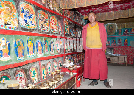 Tibetan Buddhism, monk in a room with brightly painted rock reliefs, Gossul Gompa Monastery above Lake Manasarovar - Stock Photo