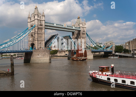 A junk passing through the opened bascules of Tower Bridge, River Thames, London, England, United Kingdom, Europe - Stock Photo