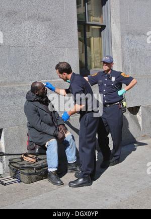 San Francisco policemen provide first aid to homeless man in the Tenderloin - Stock Photo