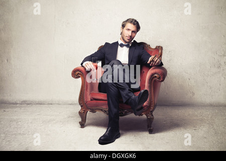 Gentleman sitting on a vintage armchair - Stock Photo