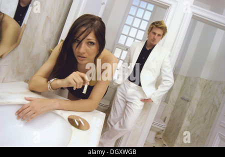 Woman snorting cocaine with a rolled bill, being watched by a man wearing a white suit and leaning on a wall - Stock Photo