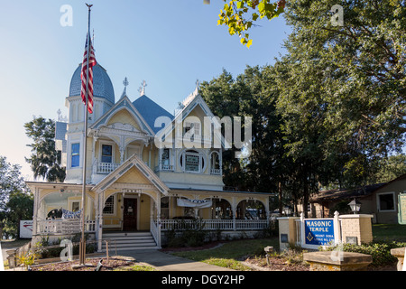 Facade of Victorian house Masonic Lodge, octagonal domed tower, wide verandas, gingerbread, ornate wood moldings - Stock Photo