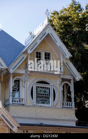 Victorian house gable end windows and wall detail with round window, gingerbread wood trim and moldings. - Stock Photo