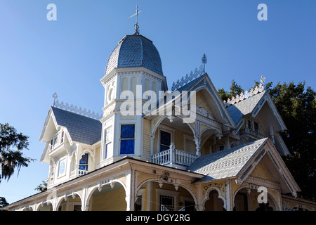 Upper facade of Victorian house with octagonal domed tower, wide verandas, gingerbread, ornate wood moldings and - Stock Photo