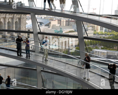 Tourists and visitors inside the dome of the Reichstag Building with views of the Brandenburg Gate, Berlin - Stock Photo