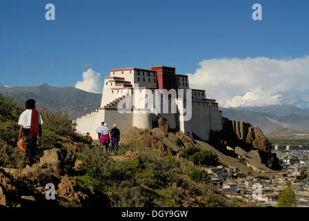 Pilgrims and a group of tourists in front of the reconstructed Shigatse Dzong Fortress, with the historic town centre - Stock Photo