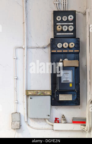 Old fuse box with an electricity meter and electrical wiring on a wall in a basement of an old building, Stuttgart - Stock Photo