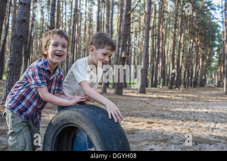 Two young boys pushing a tire in a wooded area - Stock Photo