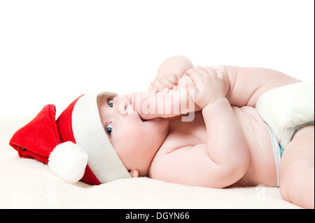 Cute six month old baby boy in Christmas hat laying on soft blanket, isolated on white background - Stock Photo
