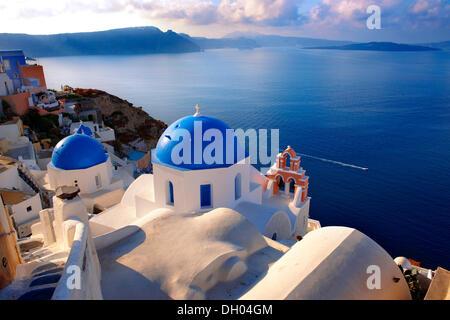 Blue domed Byzantine Orthodox churches, Oia, Ia, Santorini, Cyclades Islands, Greece, Europe - Stock Photo