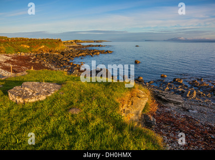 County Galway, Ireland: Morning sun on the headlands of Rinvyle Point in the Connemara Region with Inishbofin Island - Stock Photo