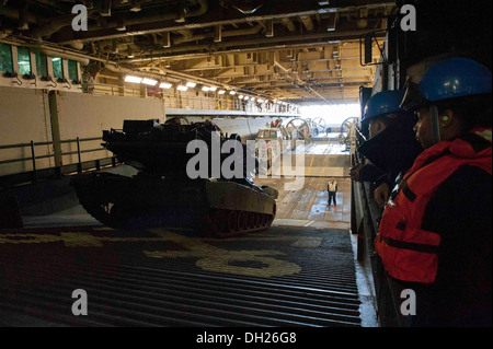 A M1A1 main battle tank drives from a landing craft air cushion (LCAC) aboard the multipurpose amphibious assault - Stock Photo