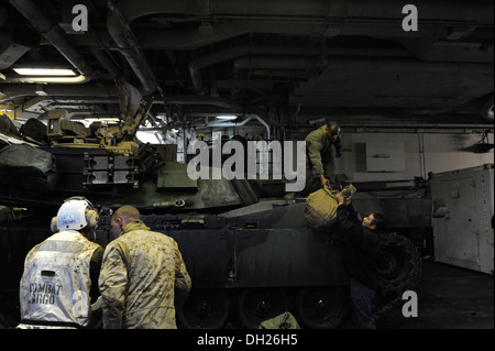 Sailors and Marines unload gear from a M1A1 main battle tank aboard the multipurpose amphibious assault ship USS - Stock Photo
