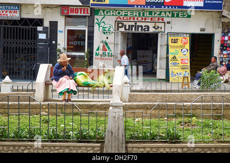 An old lady sitting on a bench on the streets of Huaraz In Peru, South America. - Stock Photo