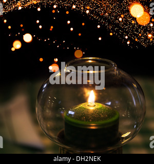 Green candle burns in candlestick made of glass with Christmas lights garland bokeh on background - Stock Photo
