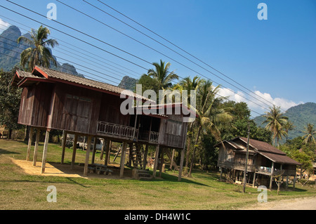Horizontal view of traditional stilted wooden houses along a countryside street in Laos. - Stock Photo