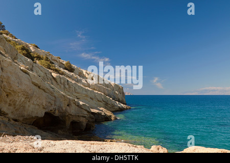 A turquoise sea and impressive formations of sandstone rock cliffs at Matala, situated on the Bay of Messara, Crete, - Stock Photo
