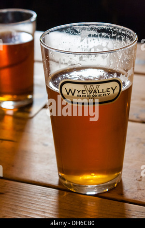 Pint of beer in a straight glass with a Wye Valley Brewery logo on a pub table. Talybont-on-Usk, Brecon, Powys, - Stock Photo