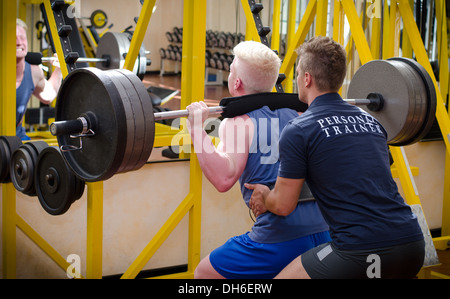 Personal trainer helping young male client in gym during workout on equipment. - Stock Photo