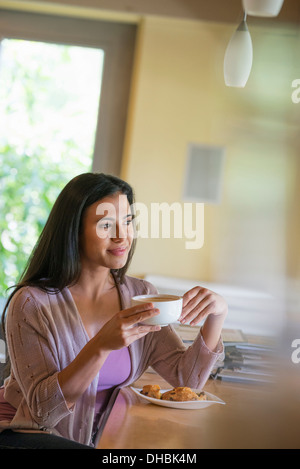 A woman having a cup of coffee. - Stock Photo