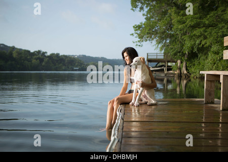 A woman with her arm around a small white dog on a jetty on a lake. - Stock Photo