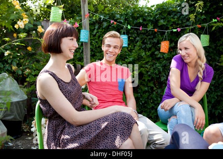 Young adult friends in garden chatting - Stock Photo