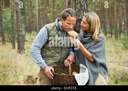 Mid adult couple foraging for mushrooms in forest - Stock Photo