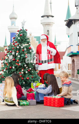 Santa Claus With Children Opening Presents By Christmas Tree - Stock Photo