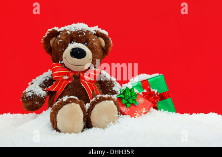 A handmade teddy bear sitting in the snow with gift wrapped Christmas presents against a red background. - Stock Photo