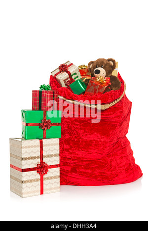 A red Christmas sack full of gift wrapped presents and toys, isolated on a white background. - Stock Photo